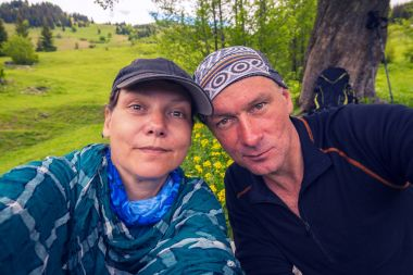Funny couple of travelers taking selfie on alpine meadow