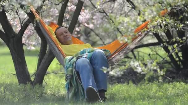 Happy man relaxes in a hammock on the green meadow under a wild blooming cherry among lush flowers, on a awesome spring day, being in harmony with nature.