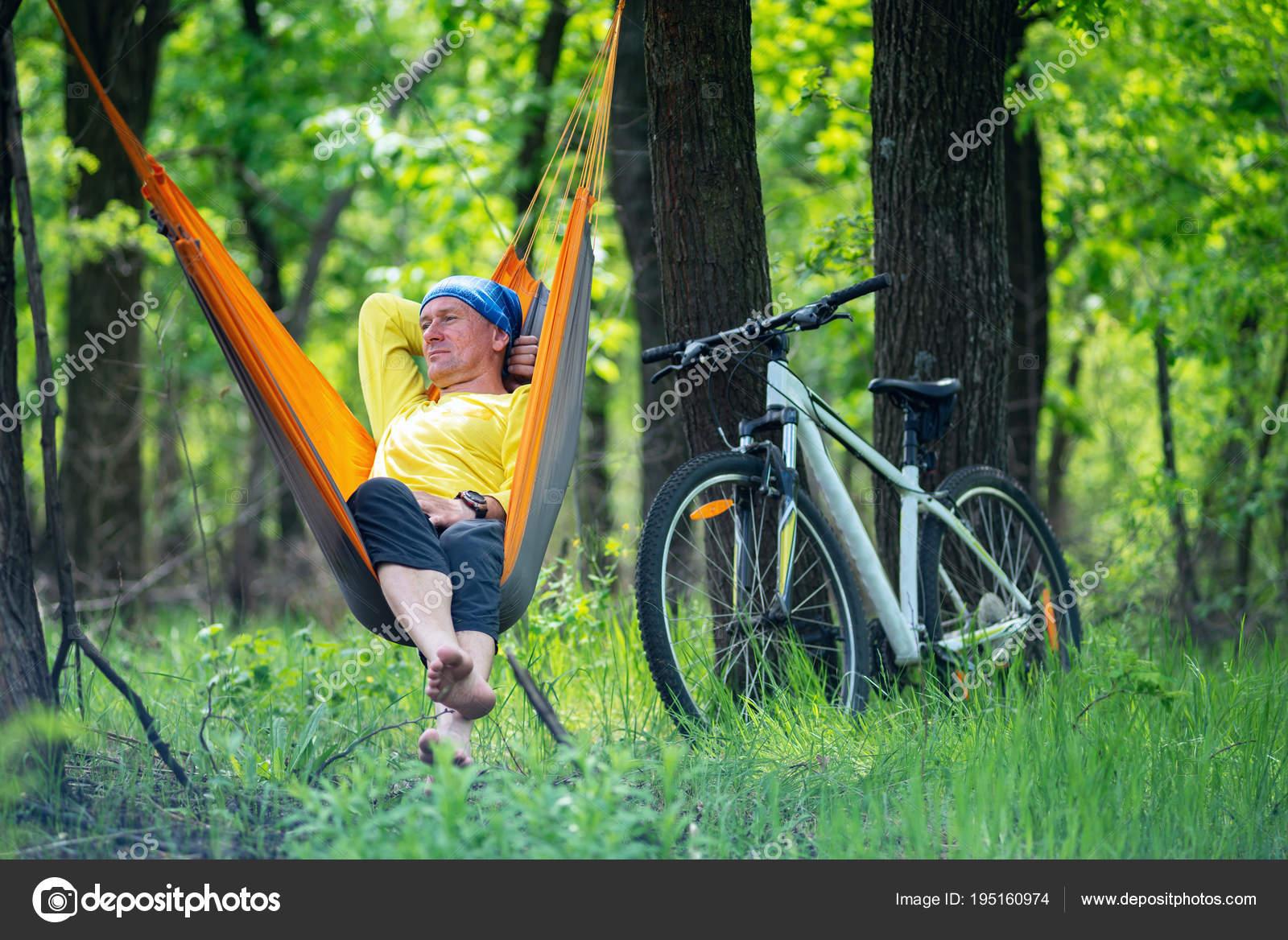 4943b6b8f2bfc Homem, descalço, relaxa e medita em uma rede na floresta depois de andar de  bicicleta em um dia ensolarado - fim de semana maravilhoso na natureza —  Foto de ...