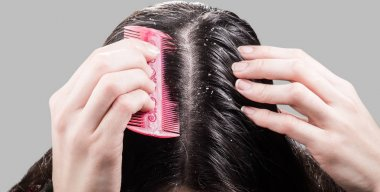 Woman removes dandruff from black hair comb