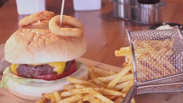 Americký cheeseburger s sýr, hovězí maso, rajče, hlávkový salát, cibule kroužky s hůlkami, hranolky a soda studený nápoj s plátkem citronu. Sklárna Nenačovice