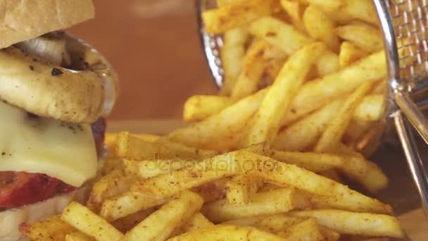 Americký cheeseburger s sýr, hovězí, rajče, hlávkový salát a žampiony, hranolky a studený nápoj soda s plátkem citronu. Sklárna Nenačovice. Zblízka zastřelil pan