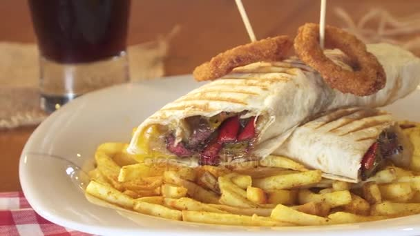 Sandwich wrap with beef meat, cheese and vegetables. Served with french fries and onion rings with sticks.