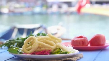 Fried calamari rings on wood blue table by the sea at Foca Izmir Turkey