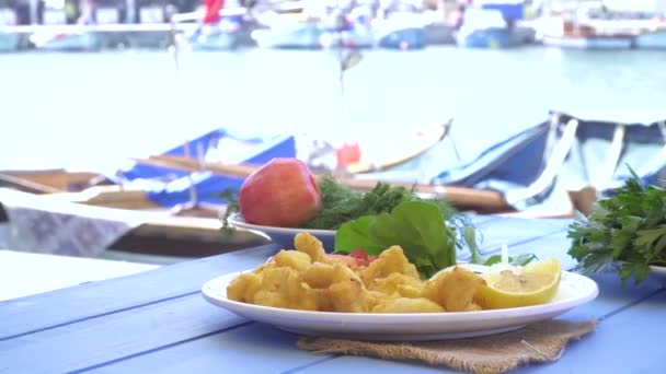 Fried seafood with lemon and arugula on blue table by the sea and small boats at small town. Izmir Foca Turkey.