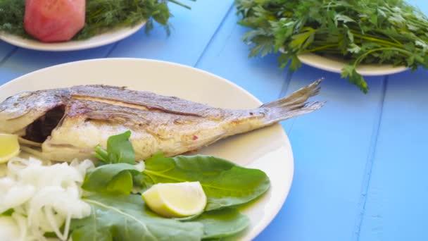 Grilovaná pražma na desce s citronem, rukolou, plátkem citronu a cibule. Zdravé jídlo. Modré stolní pozadí.