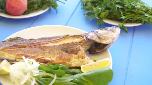 Grilovaný mořský vlk na desce s cibulí, plátky citronu a zahradní raketa aragula na modrém stole. Řecké jídlo.