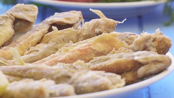 Teller mit frittierten kleinen Fisch rote Meeräsche mit Rucola und Zitrone, Nahaufnahme