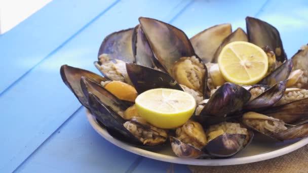 Meeresfrüchte-Gericht offen und fertig Muscheln auf blauem Tisch im Restaurant.