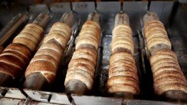 Kürtőskalács Kalacs egy hagyományos magyar földnyelv torta sült nyitott tüzet az utcában, a grillező szcénának, ünnepségek, mint esküvők és a karácsony. Lövés a lassú mozgás