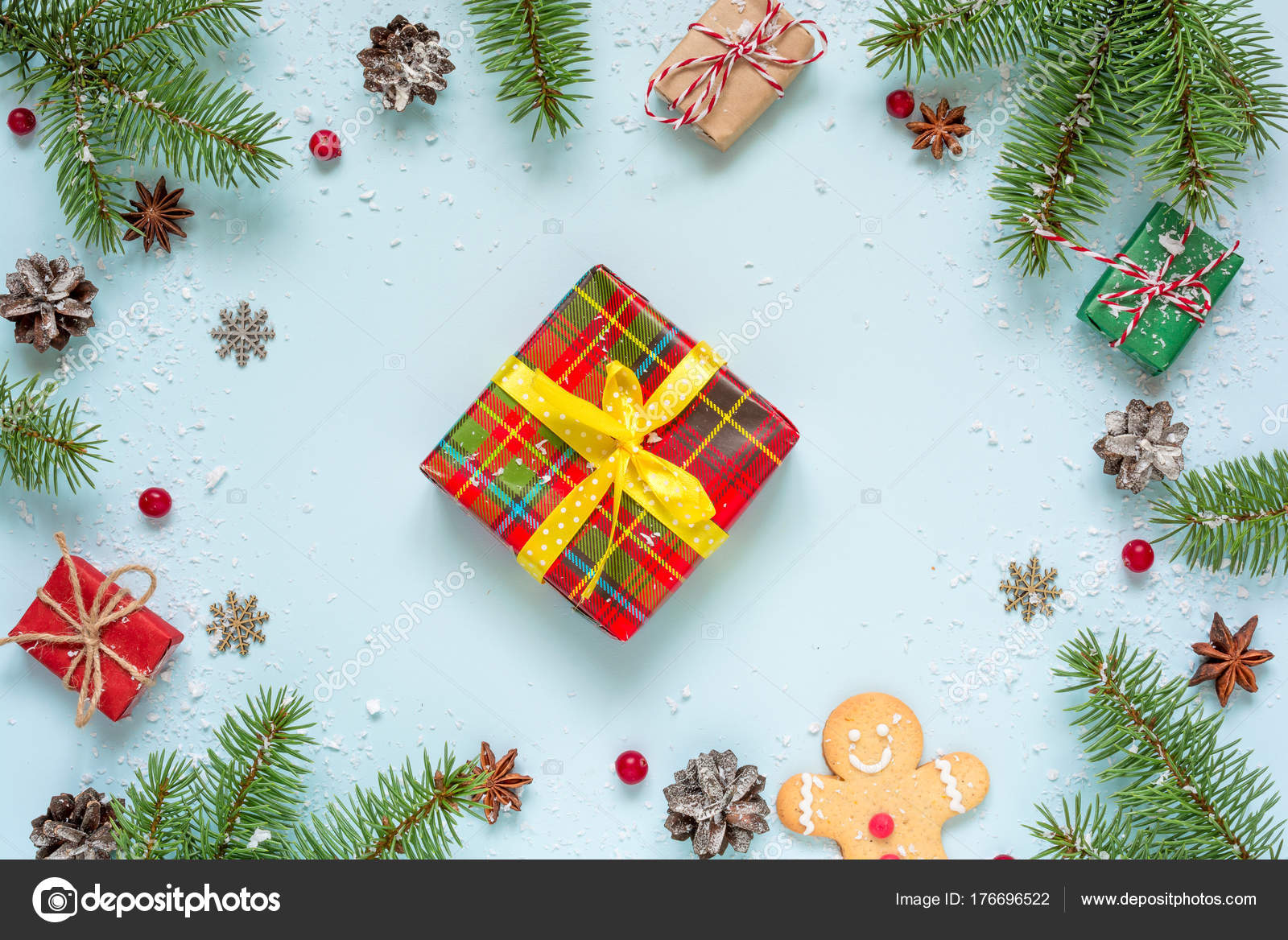 christmas composition frame made of fir tree decorations red berries gift boxes and pine cones on blue background christmas background