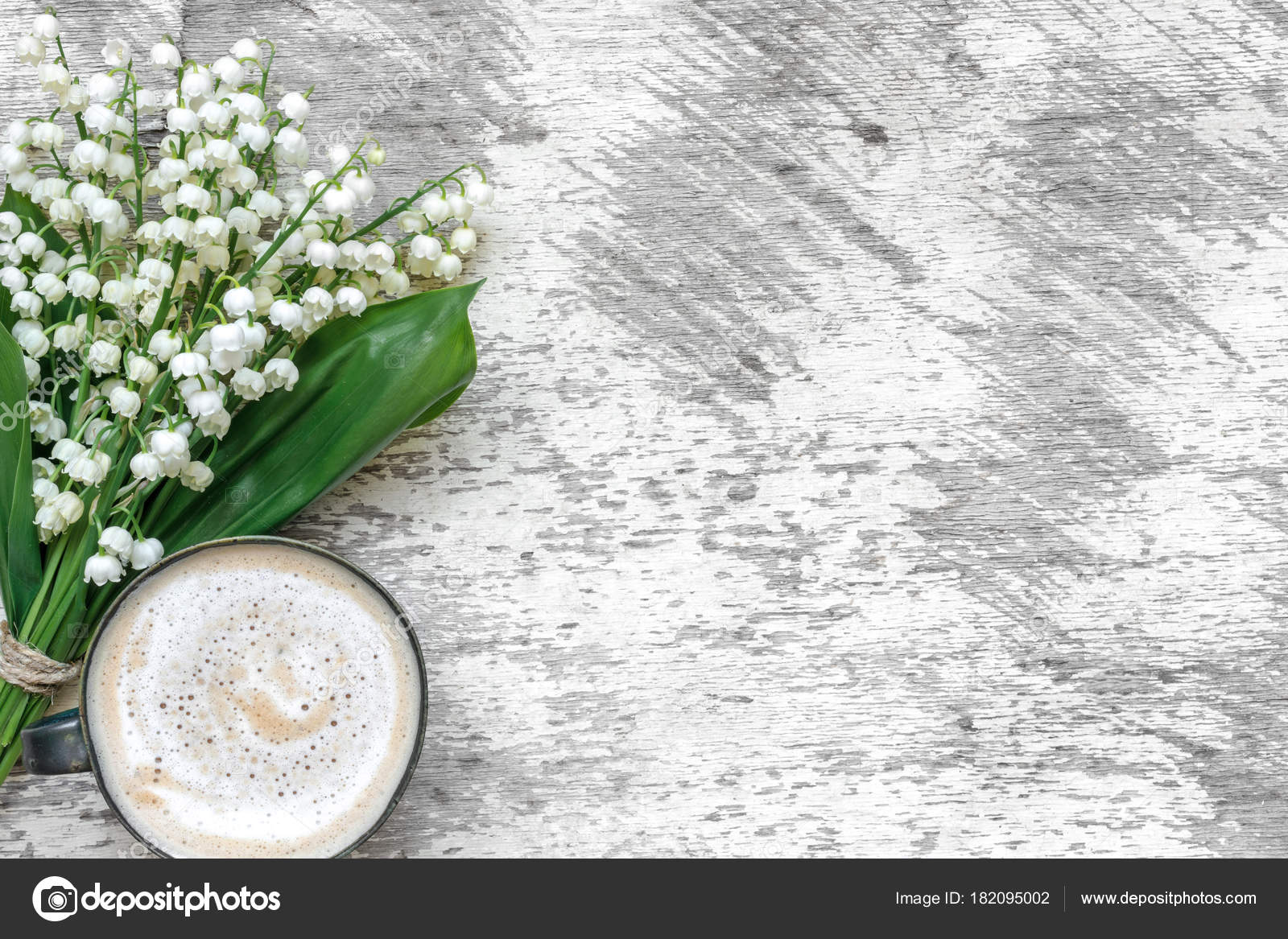 Cup of cappuccino with spring lily of the valley flowers over white cup of cappuccino with spring lily of the valley flowers over white wooden table stock mightylinksfo