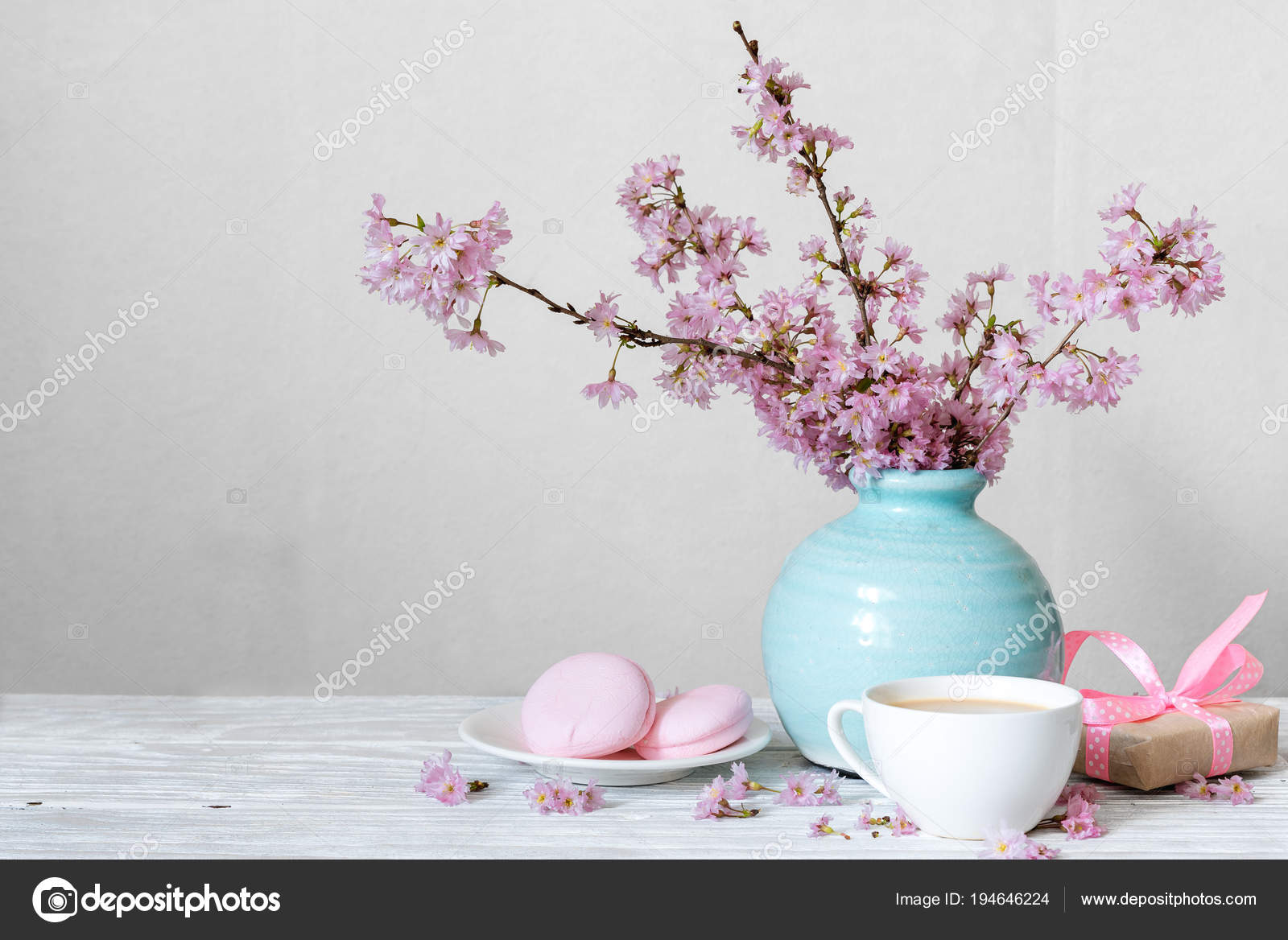 Pink cherry blossom flower bouquet with coffee cup, macarons and ...