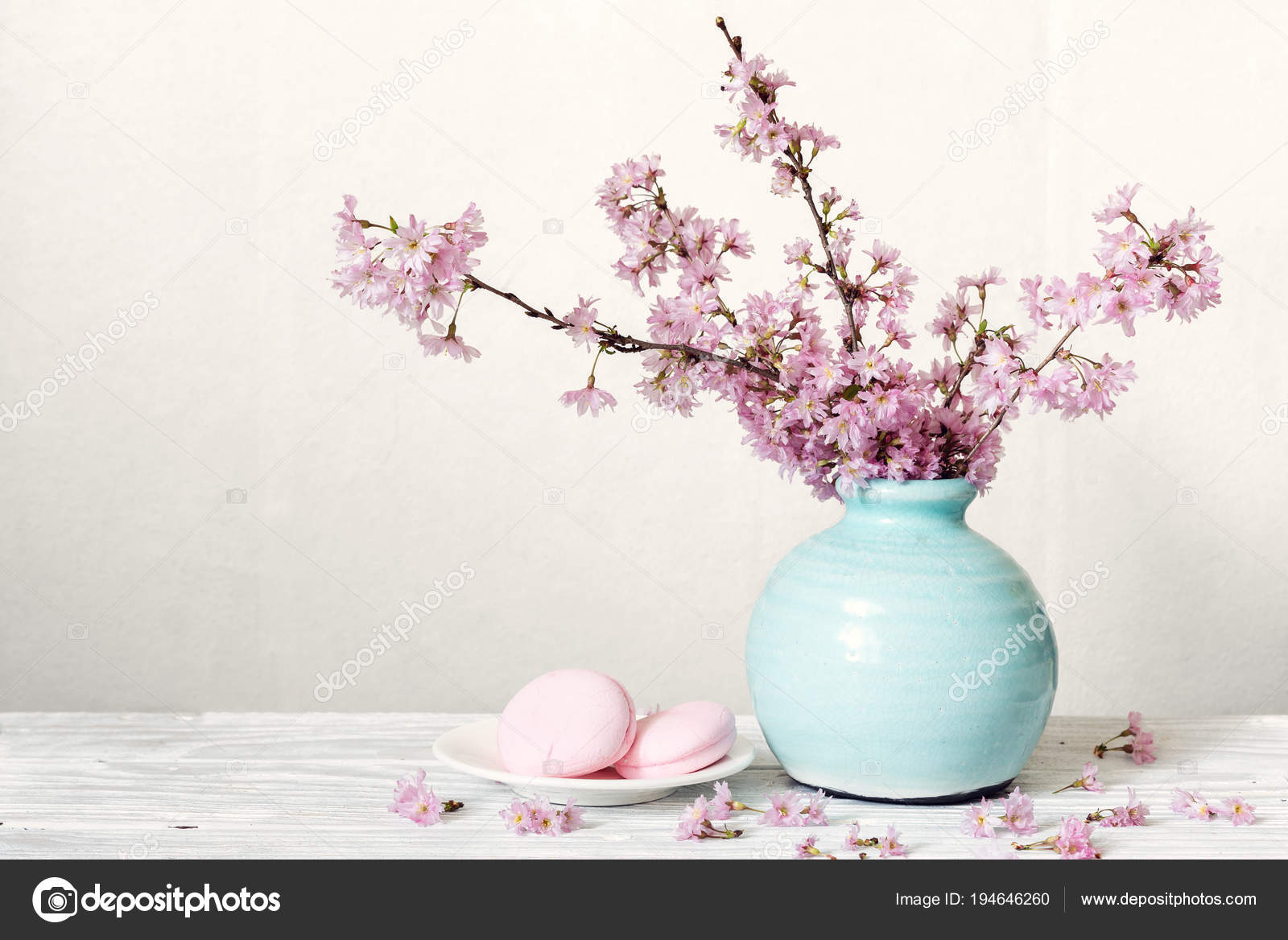 Pink cherry blossom flower bouquet with macarons in blue vintage ...