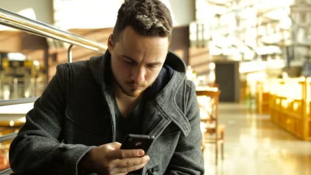 Mann telefoniert in einem Café in einem großen Einkaufszentrum.