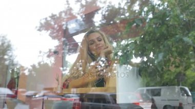 Girl listening to music in modern cafe . Street traffic is on window reflection