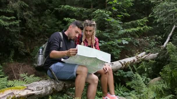 A guy and a girl in the woods are looking for a road with a map