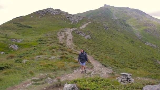 Hiker hiking in beautiful landscape. Man trekking walking with backpacks in mountains
