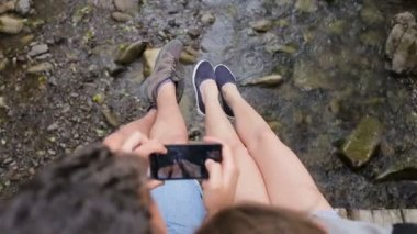 Young couple of tourists with backpacks on a bridge over a mountain river. Make a photo of the feet on the background of the river