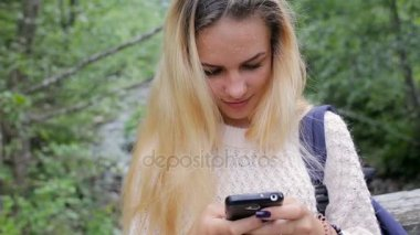 Young girl with a phone on a bridge over a mountain river