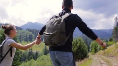 A couple climbing a mountain range, raise their hands up for joy