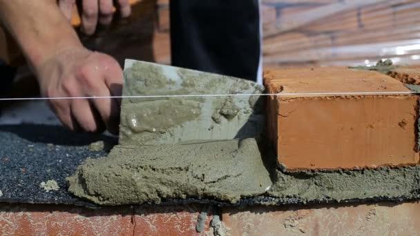 Práce klade cihly na staveništi na čerstvém vzduchu