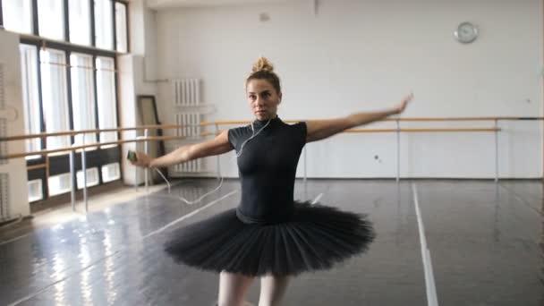 die Ballerina übt im großen Saal und hört Musik auf dem Smartphone