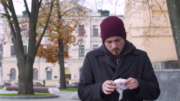 Sick man blowing nose in cold weather, slow motion