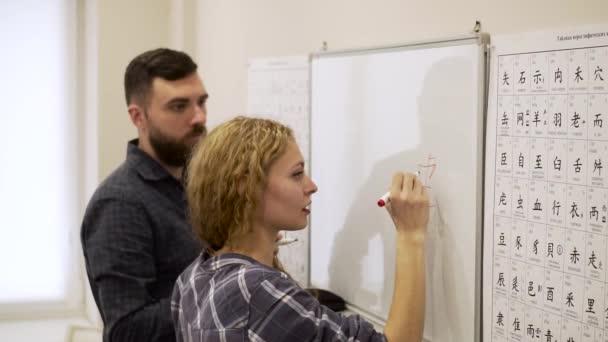 Středně mladý muž pomáhá dívka učit čínské znaky v kanceláři