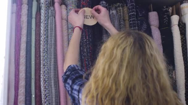 Mladá krásná žena zvolí látku v textilním obchodě