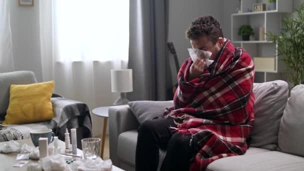 Nemocný se vysmrká do ubrousku v obýváku.