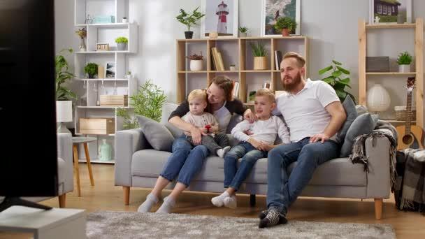 Rodinné sledování televize, zatímco sedí na gauči v obývacím pokoji