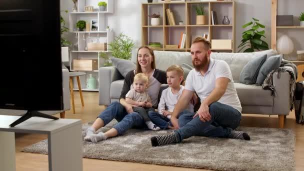 Rodinné sledování televize, zatímco sedí na podlaze obývacího pokoje
