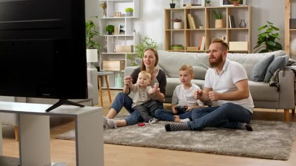A boy with a gamepad plays video games with dad, mom and little brother