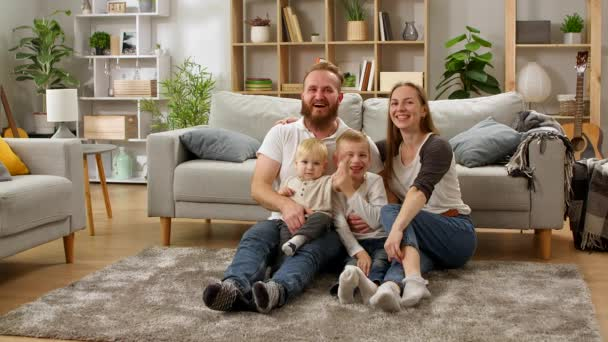 Portrait of a young cheerful family at home on the living room floor