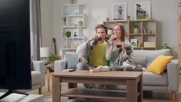 Young couple watching tv and drinking coffee with donuts hiding in a blanket