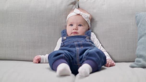 Malá holčička sedící na pohovce v obývacím pokoji