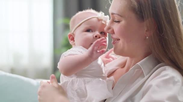 Máma líbá a objímá malou dcerku v ranním slunci