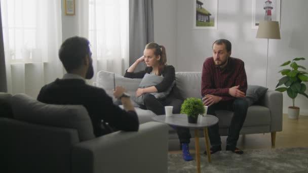 Mladý pár v kanceláři rodinného psychoanalytika. Psycholog doporučuje
