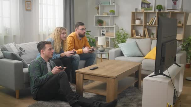 Three friends play video games while sitting on a couch in a living room