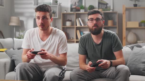 Két fiatal férfi játszik számítógépes játékok segítségével gamepads