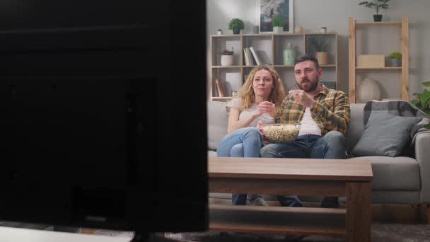 Mann und Frau schauen Comedy im Fernsehen und essen Popcorn.