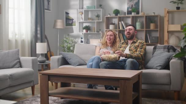 Couple watching tv while sitting on a sofa and eating popcorn