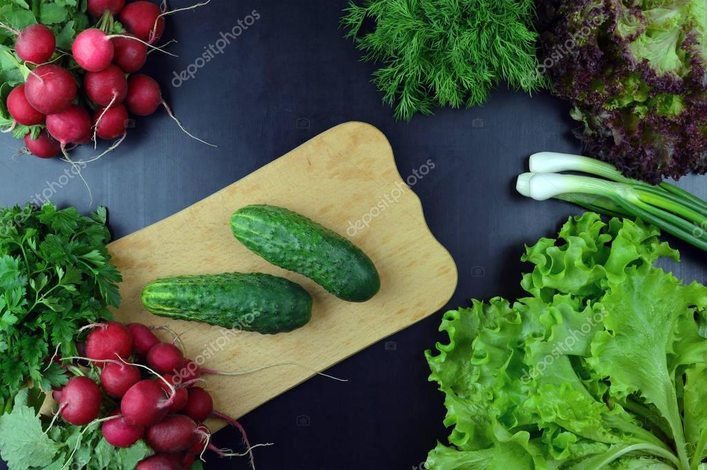 Cucumbers and fresh vegetables on a cutting board. Top view.