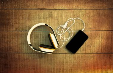 Smartphone and headphones on a wooden background. Listen to musi