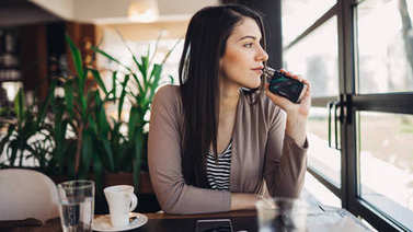 Young woman using electronic cigarette to smoke in public places.Smoke restriction,smoking ban.Using vaping device with flavoured liquid.E-juice vaping.Smoking habit,nicotine addict,tobacco industry