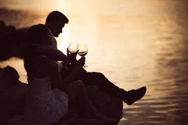 Romantic couple drinking wine at sunset at a pier on a seaside.Romance.Two people having a romantic evening with a glass of wine near the sea.Enjoying company.Celebrating anniversary.Honeymoon