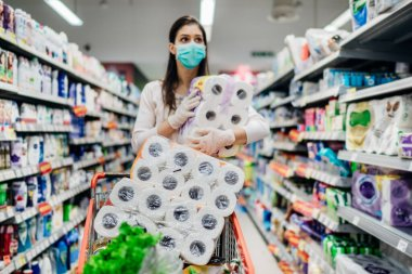 Toilette paper shortage.Woman with hygienic mask shopping for toilette paper supplies due to panic buying and product hoarding during virus epidemic outbreak.Hygiene products deficiency stock vector