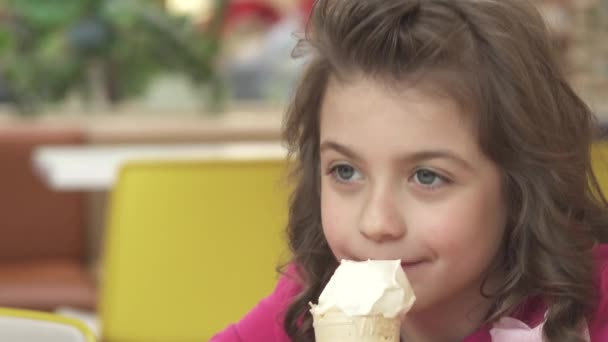 Šťastný a spokojený holčička jíst zmrzlinu v kavárně
