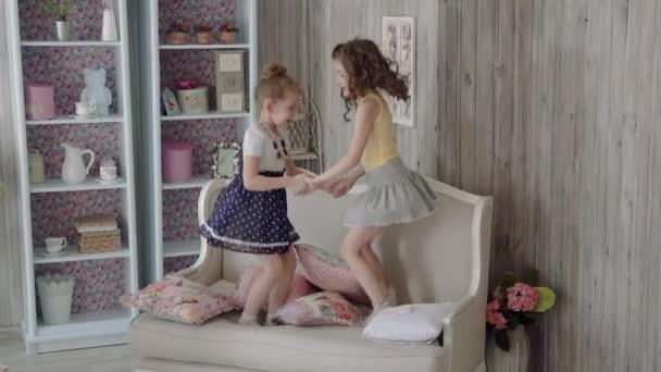 malé holky kamarádky skákat na gauči a play. dívka se dostane z postele. Zpomalený pohyb